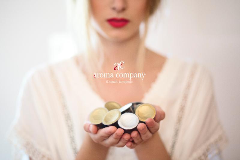 ragazza mostra capsule caffè di qualità Aroma Company un mondo creativo